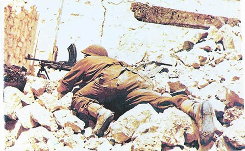 Sgt Carr 1st Somerset Light Infantry using Bren gun in the ruins of Cassino town. (Note the hole in right boot!)